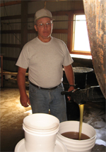 Lynn Haitt, Haitt and Sons Honey Company, pours Alfalfa Honey