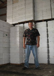 Beekeeper Stan Kolesnikov in front of a few of his stored honey supers