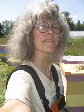 Beekeeper in Tee-Shirt while cutting grass at hives